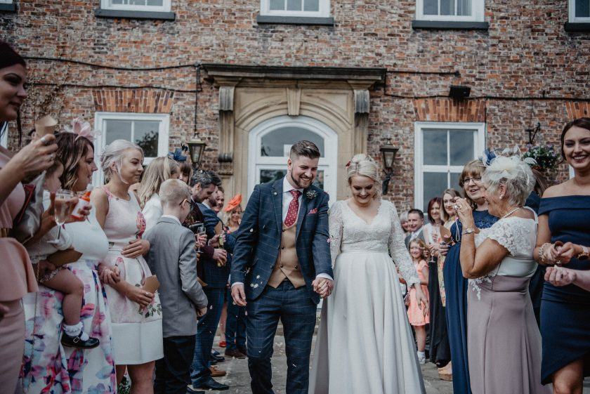 The Bride and Groom Walking through the crowd, Photography by Claire Hirst Photography